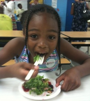 A student at Beers Elementary in Southeast enjoys Salad and Strawberry day.