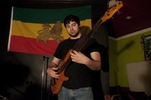 Brian Waitzman plays with pop-Americana singer Flo Anito at Almaz on Sunday. An Ethiopian flag hangs behind him.